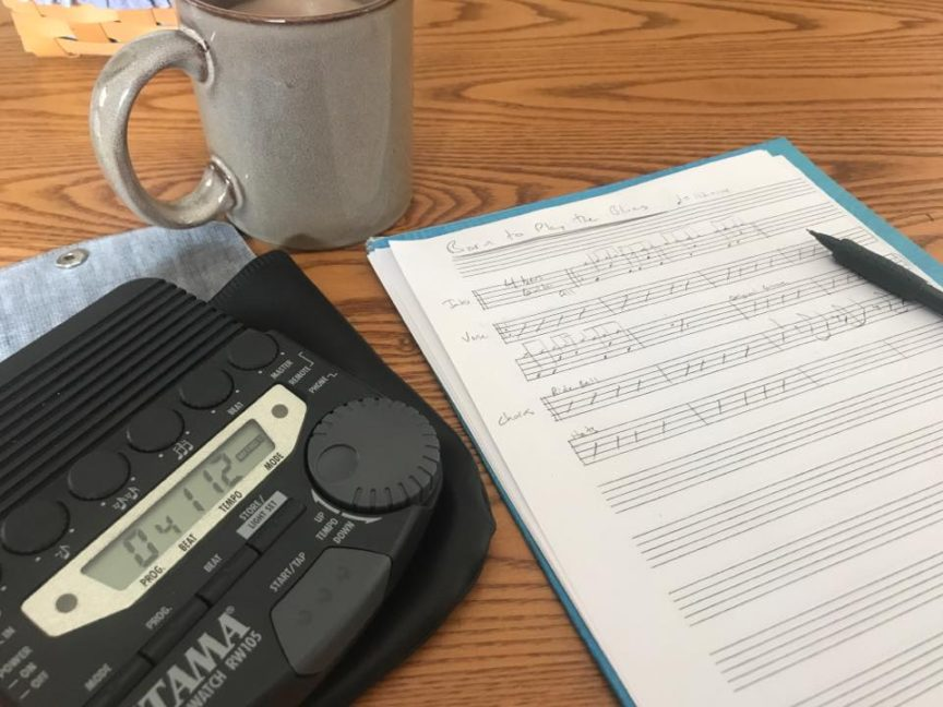 the image shows music staff paper with a pencil, metronome, and cup of coffee
